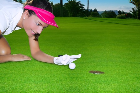 flicking: Golf green hole course woman humor flicking hand a ball inside in short putt