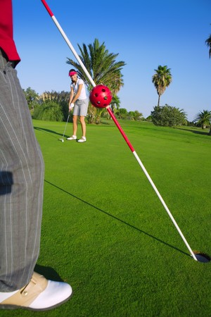 golf woman player putting golf ball and man holds flag photo