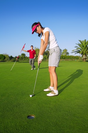 woman golf: golf woman player green putting hole golf ball a man holding flag