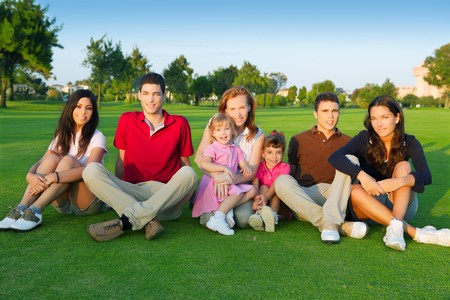 family friends group people sitting green grass outdoor with children photo