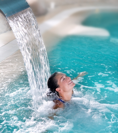 spa: spa hydrotherapy woman waterfall jet turquoise swimming pool water Stock Photo