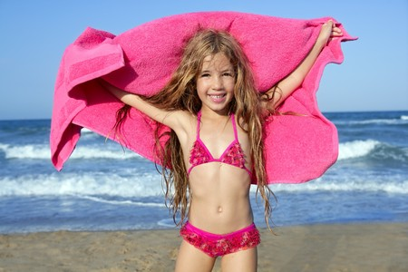 kids playing beach: Beach little girl playing pink towel and wind in blue sea Stock Photo