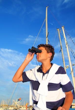 binoculars teenager boy on boat marina in blue summer vacation photo