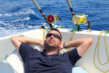 resting rod fishing: Sailor man fishing resting in boat summer vacation blue sea