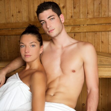 Sauna spa therapy young couple in warm wooden room white towel photo