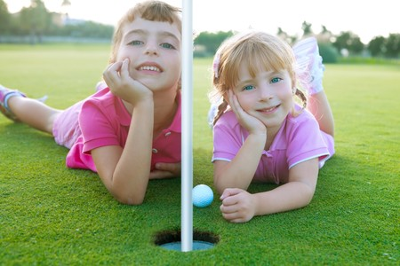 Golf two sister girls relaxed lying near green hole with ball Stock Photo