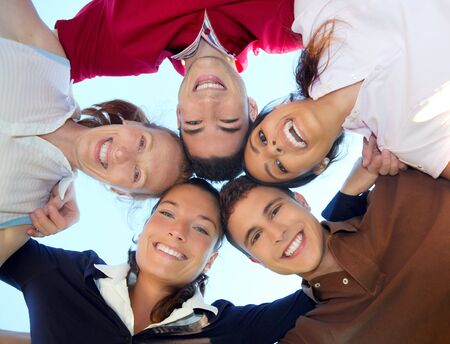 ниже: friends happy group in circle heads smiling together from below view