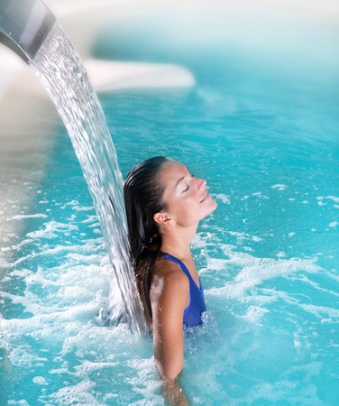 hydrotherapy: spa hydrotherapy woman waterfall jet turquoise swimming pool water Stock Photo