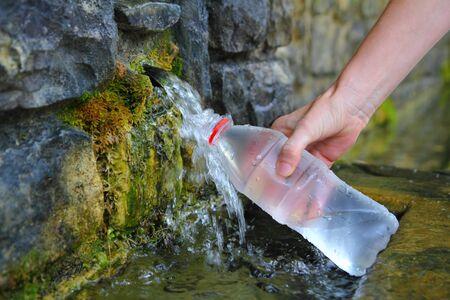 source d eau: source d'une bouteille d'eau au printemps remplir main tenant en Pyr�n�es Banque d'images