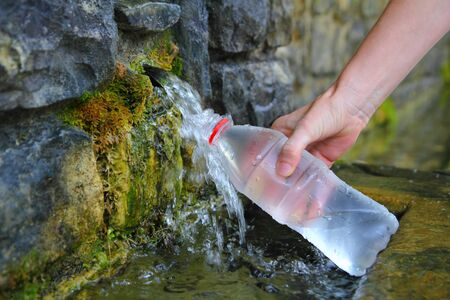 source of spring water bottle filling holding hand in Pyrenees mountain Stock Photo - 8289064