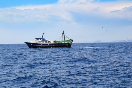 fishing trawler professional boat working in blue ocean sea photo