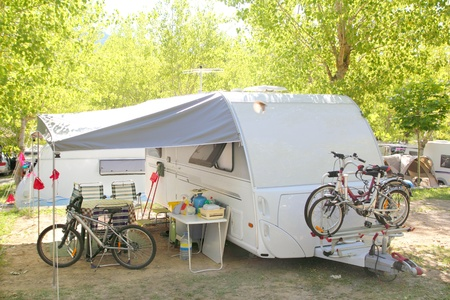camping: Camping camper caravan trees park with bicycles Stock Photo