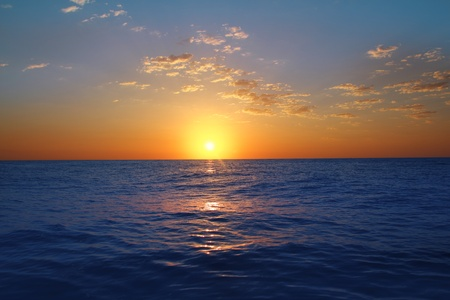 Sunrise sunset in ocean blue sea horizon glowing orange\ golden sun