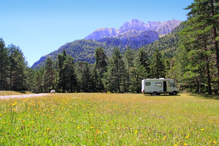 Camper autocaravan meadow in Pyrenees mountain sunny day pine trees forest Stock Photo - 8289327