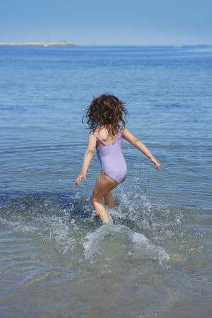 brunette little girl running into beach water back view summer vacation photo