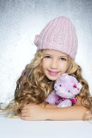 winter fashion cap little girl hug teddy bear smiling silver background photo