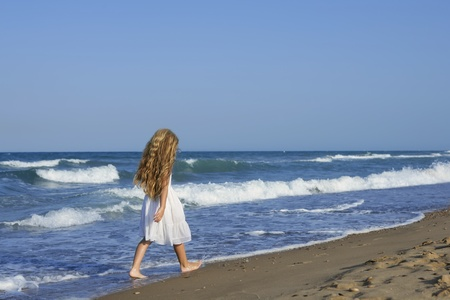 Little girl running beach shore splashing water in blue sea Stock Photo - 8288875