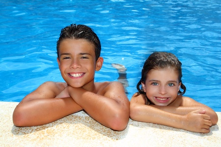 teen boy and little girl summer vacation in blue swimming pool Stock Photo - 8289041