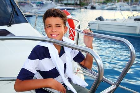 teenager boy sea marina summer vacation sitting in boat bow as sailor photo