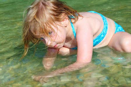blond girl swimming in lake river beautiful blue eyes child photo