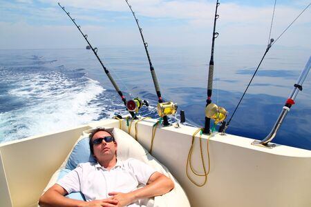 Sailor man fishing resting in boat summer vacation blue sea photo