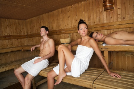 Sauna spa therapy beautiful young people group in warm wood room white towel photo