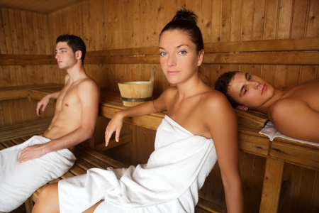 Sauna spa therapy young people group in warm wooden room white towel photo