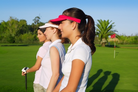 woman golf: Golf three woman in a row green grass course players Stock Photo