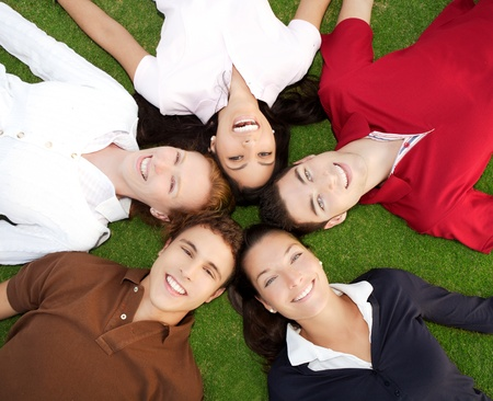 friends happy group in circle heads together on green grass outdoor photo