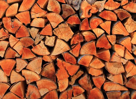 firewood wood pile stacked triangle shape red color photo