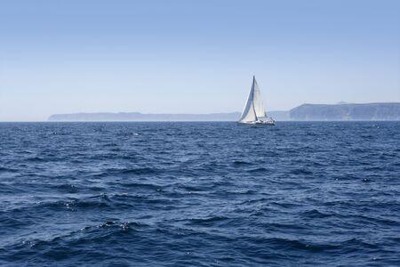 rough sea: Blue sea with sailboat sailing the ocean surface