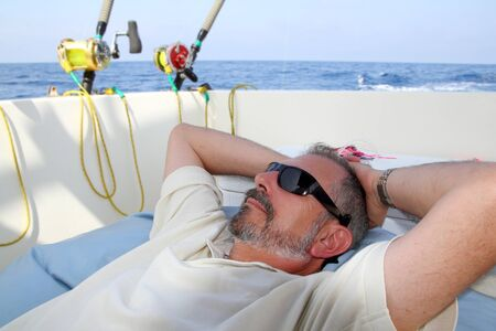Sailor senior fisherman relax on boat fishing deep sea photo
