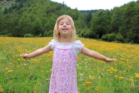 Open arms girl in beautiful flower spring meadow in Pyrenees mountains Spain photo