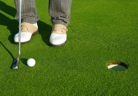 spacing: Golf green hole course man putting ball inside short putt Stock Photo