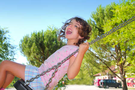 Girl swinging swing in outdoor park nature low angle view photo
