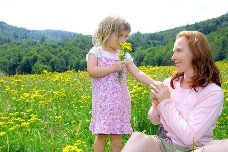 Daughter and mother playing in spring flowers meadow outdoor Stock Photo - 8385073