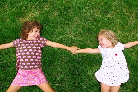 to lie: two sister girls lying on meadow green grass like friends playing