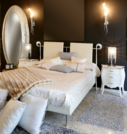bedroom: bedroom modern silver oval mirror white bed black wall Stock Photo