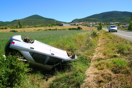 damaged roof: Car crash accident upside down vehicle off the road green landscape
