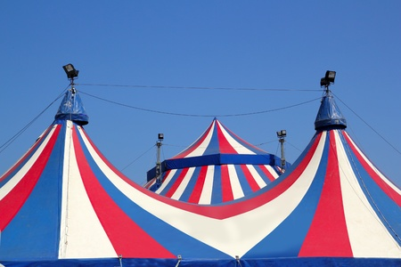 Circus tent under blue sky colorful stripes red white photo