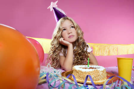 bored little blond girl in a birthday party with cake and candle on pink background Stock Photo - 8425944