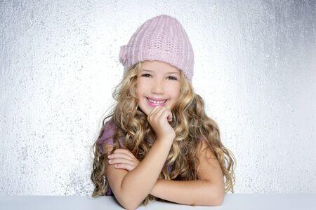 Smiling gesture little girl winter pink cap portrait silver background photo