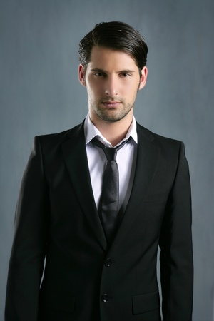 Fashion trendy elegant young black suit man posing looking camera photo