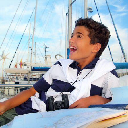 boy teen sailor laying on marina boat chart map smiling in summer vacation photo