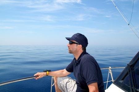 sailboat race: Sailor man sailing boat blue calm ocean water Mediterranean sea