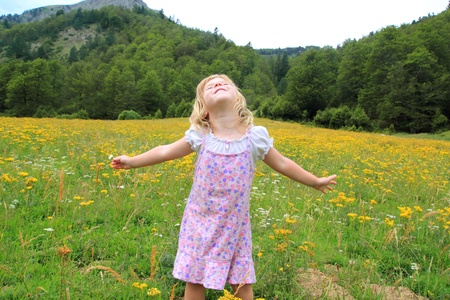 pyrenees: Open arms girl in beautiful flower spring meadow in Pyrenees mountains Spain Stock Photo