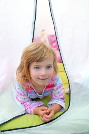 girl in camping tent lying happy on camp tent photo