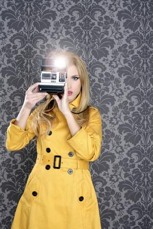 60s fashion: fashion photographer retro camera reporter woman vintage wallpaper yellow coat Stock Photo