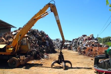 recycling plant: scrap metal scrap-iron junk outdoor with crane Stock Photo