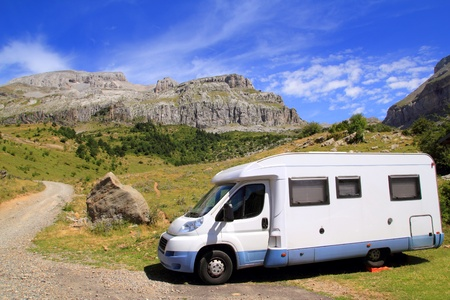 Camper van in mountains blue sky nature sunny outdoor photo